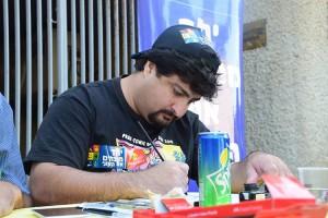 יושב ומצייר באירוע אומנות ונתינה של קומיקס וירקות ולתת.